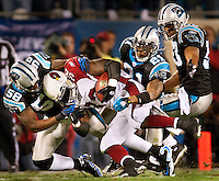 Carolina Panthers Thomas Davis (58) Ken Lucas (21) and Na'il Diggs (53) try to tackle Arizona Cardinals running back Edgerrin James (32) during the NFC Divisional Playoff football game at Bank of America Stadium, in Charlotte, NC. Arizona defeated the Carolina Panthers 33-13.