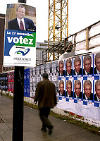 Montreal, November 27th, 2000<br /> A pedestrian in downtown Montreal.(Quebec, CANADA) walks between <br /> A poster for Canadian Reform Alliance Progressive Party (CRAPP) leader Stockwell Day and a  row of posters for Bloc Quebecois leader Gilles Duceppe<br /> Latest polls give about 25 % of the vote to Day and 10 % to Duceppe .