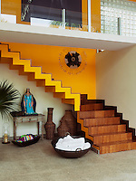 The open staircase mixes a wood finish with bright yellow paint whilst the space underneath is used as a display area with a large wok filled with rolled towels