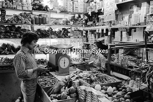 Asian grocery shop Brick Lane. Boy serving customer in family run shop. East London 1970s Britain ..