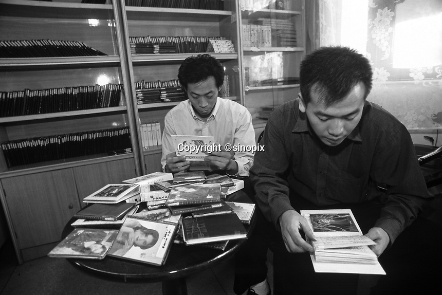 Unmarried men looks  at books of women for potential brides at the Heart to Heart Dating Agency in Guangzhou, China. An average gender inbalance 120 males to 100 females caused by the Chinese Governments One Child Policy and the  preference for boys means that there is a shortage of women brides in China with men increasingly looking to matching agencies to find a bride.<br /> May 2000<br /> <br /> photo by Richard Jones / Sinopix