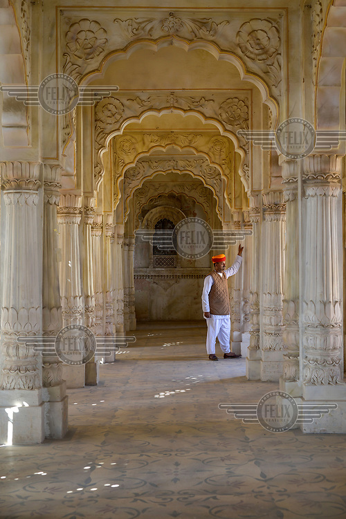 A uniformed palace guard/attendant stands in an ornate arcade, this one not open to tourists, typical of the elaborate interior design inside Mehrangarh Fort/Palace.
