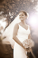Sepia toned photo of bride with bouquet, smiling looking back over her shoulder with veil blowing in the wind