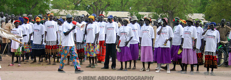 Organized by the international NGO, Population Services International (PSI), men and women from two Dinka folklore groups gather in Rumbek's Freedom Square to talk about malaria prevention on Africa Malaria Day.