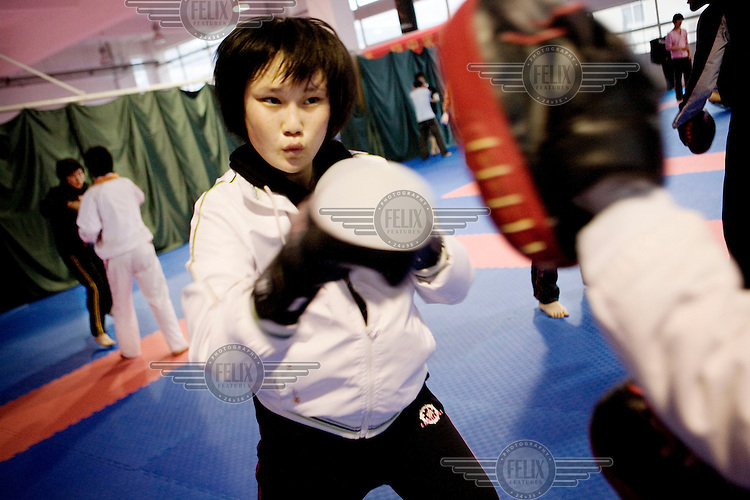 """Tae Kwon Do and boxing class at the Qingdao City Sports School, one of the country's top breeding grounds of Olympic athletes. There is an emphasis in the sports programme to focus on the newer and slightly less well known Olympic sports because strategically it is deemed easier to win more gold medals in these areas. Principal Qiao Xiangdong credits the Beijing 2008 Olympic Games for spurring the local government to build a USD 42 million new campus for the academy's 600 students. """"Before, some parents were worried about sending their kids to sports schools because they thought their children would have to eat too much bitterness,"""" Qiao says, using the Chinese term for enduring hardship. """"But the Olympic Games have made people willing to contribute to the nation's glory."""""""
