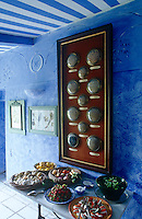 Under the blue and white striped ceiling In the kitchen an antique collection of dried flowers hangs above a side table laden with good things to eat