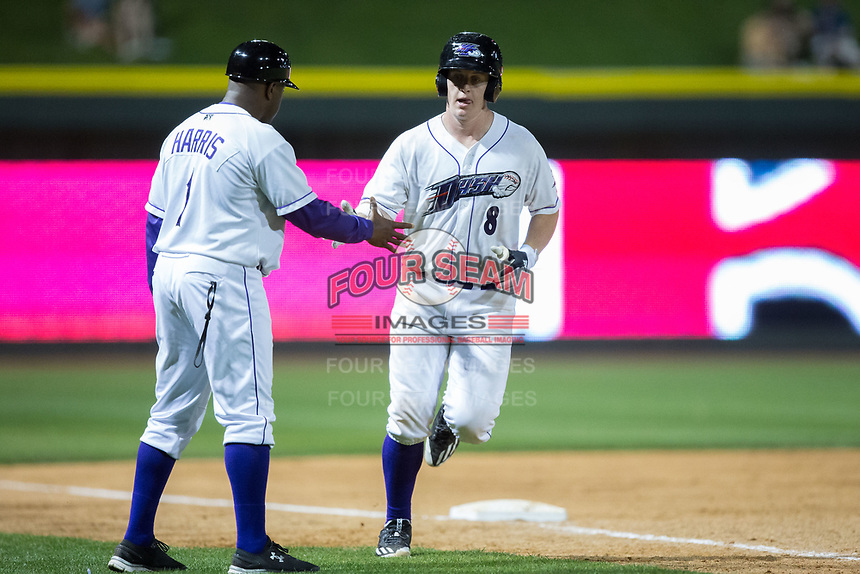 Winston-Salem Dash manager Willie Harris (1) shakes hands with Zack Collins (8) as he rounds third base after hitting a home run against the Myrtle Beach Pelicans at BB&T Ballpark on May 11, 2017 in Winston-Salem, North Carolina.  The Pelicans defeated the Dash 9-7.  (Brian Westerholt/Four Seam Images)