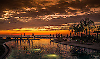 Fine Art Landscape Photograph. Sunset on Banderas Bay, Puerto, Vallarta, Mexico. Silhouette The Grand Venitian Pool with people in the pool looking at the golden rays of the setting sun.