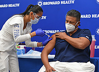 FORT LAUDERDALE, FL - DECEMBER 23: Leonida Lipshy, RN in the COVID unit at the Broward Health Medical Center, gives Jaime Carrillo, M.D. Internal Medicine, Broward Health Imperial Point, a shot of the Moderna COVID-19 vaccine as Broward Health begins Vaccinating frontline Healthcare caregivers with the Moderna COVID-19 vaccine at Broward Health Medical Center Imperial Point on December 23, 2020 in Fort Lauderdale, Florida. <br /> CAP/MPI04<br /> ©MPI04/Capital Pictures