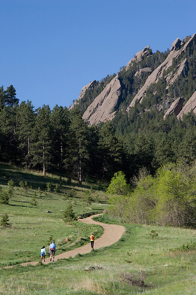 Caucasian male and female hikers and the Flatirons rock formation, Chautauqua Park, Foothills, Boulder, Colorado, USA .  John leads hiking and photo tours throughout Colorado. .  John leads hikes and private photo tours in Boulder and throughout Colorado. Year-round.
