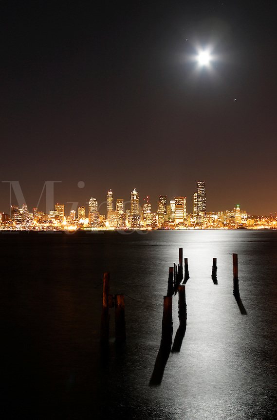 Full moon rising over Seattle city skyline at night, pilings silhouetted by moon light reflected in Elliot Bay, Seattle, Washington, US