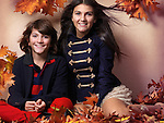Smiling boy and a teenage girl in trendy clothes sitting together surrounded with red autumn leaves beautiful artistic fall fashion photo Image © MaximImages, License at https://www.maximimages.com