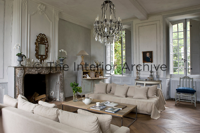 A rare 18th century provencal mirror hangs above the original marble fireplace in the salon which is furnished with a pair of hemp-covered contemporary sofas and a simple iron-framed coffee table