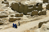 A family walk through a part of Kabul totally destroyed by war. Kabul,Afghanistan,Asia.