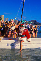 Crowds await Santa's arrival by outrigger canoe on Christmas Eve at Waikiki Beach behind the Halekulani hotel.