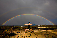 Young woman practicing yoga pose at Shark's Cove on the North Shore of Oahu, with a double rainbow in the background