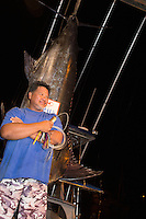Bomboy Llanes, captain of the fishing boat Lana Kila, stands in front of a Pacific blue marlin grander at Honokohau Harbor, Big Island; he holds the Bomboy Lure that was used to catch the 1,041-lb. fish.