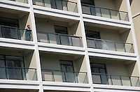 A construction worker rests on the balcony of an unfished apartment complex in Shanghai, China. The city government has recently implemented a series of mortgage and real-estate transaction regulations in hopes of cooling down the rapidly rising real-estate value and cut down in speculation..04-APR-05