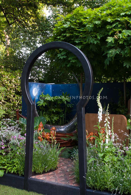 Moon gate, painted garden wall with night sky and stars, perennials, flowers, trees