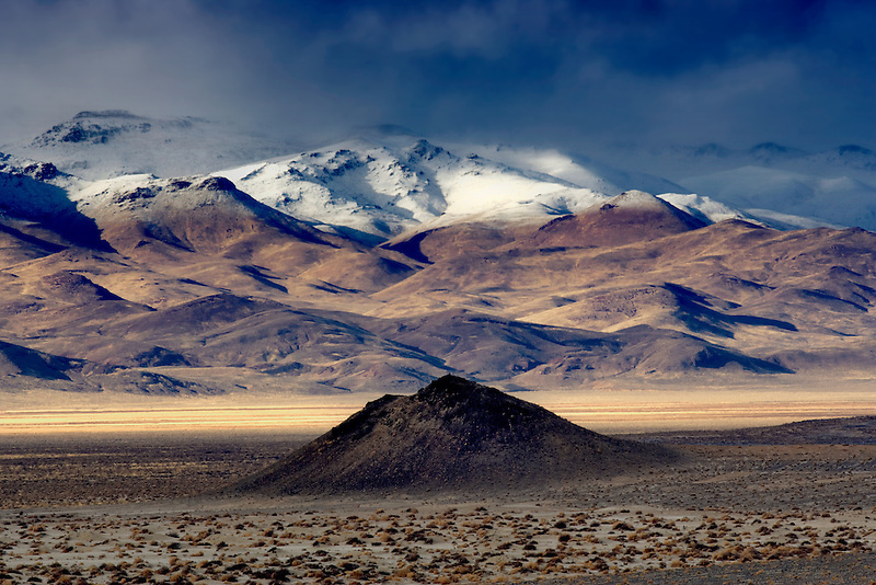 Small cinder cone and snow covered mountains. Black Rock Desert National Conservation Area. Nevada