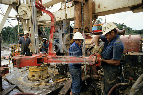 Amazonas State, Brazil. Petrobras oil exploration site in the rainforest; four workers at the drill rig; Caraoari.