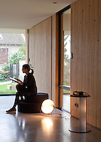 The owner of this modern house perches on a contemporary pouffe in the living area