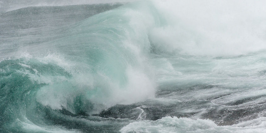 A large Lake Superior wave crashing ashore during an April snow storm. Marquette, MI