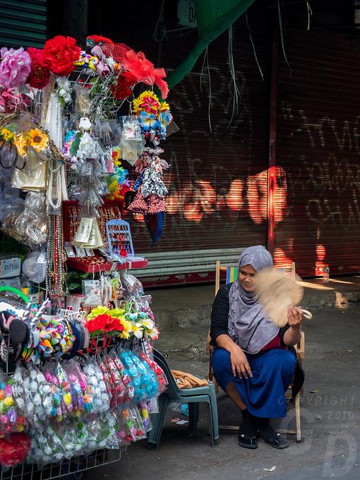 Muslim women street Vendor during Easter Good Friday near a church Street Photography, Manila, Philippines