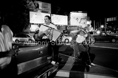 Culiacan, Sinaloa.Mexico.July 5, 2008..Musicians who play narco corridos, or drug ballads, wait on the street at night in hopes of being picked up to play at private parties. Work has become more difficult since the recent spike in violence. Fewer people hold parties. From January 1 to mid-July 2008 there have been 535 drug related killings in Sinolao, many of them were police officers..