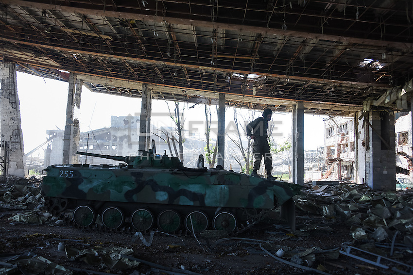 A Russia-backed rebel on an infantry tank in ruind of Donetsk airport, eastern Ukraine, Friday, June 12, 2015