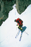 Man making a ski descent between rocks through the snow from Mount Sill in the Palisade Range, High Sierra, California.