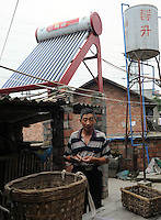 A farmer with a solar panel  at Xiao Jiao village next to the Dong Qi Emei Polysilicon Project near Leshan, Sichuan, China, that have been damaged by gasses leaking from the plant. The villagers complain of contaminated vegetables and poisoned air and ground water from the plant.