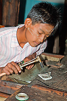 Myanmar, Burma.  Young Man Heating Metal Priot to Forming it into a Ring, Inle Lake, Shan State.  He is wearing traces of thanaka paste on his face, a Burmese cosmetic sunscreen.