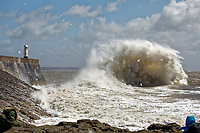 Waves crash against the promenade wall and lighthouse in Porthcawl, caused by strong winds during storm Hannah in south Wales, UK. Saturday 27 April 2019