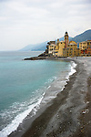 The beach of Camogli with gray and black pebbles and the view to the church / Basilika di Santa Maria Assunta and the castle / Castel Dragone. Blue water contrasting the warm tones of the houses.