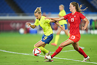 YOKOHAMA, JAPAN - AUGUST 6: Nathalie Bjorn #14 of Sweden and Jordyn Huitema #19 of Canada battle for the ball during a game between Canada and Sweden at International Stadium Yokohama on August 6, 2021 in Yokohama, Japan.