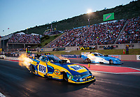 Jul 19, 2019; Morrison, CO, USA; NHRA funny car driver Ron Capps (near) races alongside Tommy Johnson Jr during qualifying for the Mile High Nationals at Bandimere Speedway. Mandatory Credit: Mark J. Rebilas-USA TODAY Sports