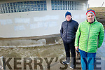 Kevin Williams and Mike O'Neill at the wall near the bathing slip in Fenit covered in political graffiti on Monday.