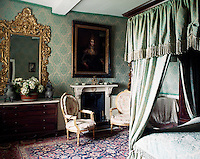 The walls of this bedroom, furnished with a four-poster bed and a pair of Louis XIV bergeres, are covered in gold and green damask
