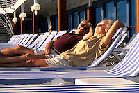 Mature couple relaxing on  cruise lounge chairs