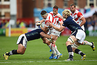 Luke Thompson of Japan is tackled. Rugby World Cup Pool B match between Scotland and Japan on September 23, 2015 at Kingsholm Stadium in Gloucester, England. Photo by: Patrick Khachfe / Stewart Communications