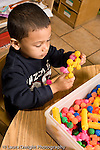 Education preschoool children ages 3-5 manipulatives boy working alone playing with colored connecting plastic pieces vertical