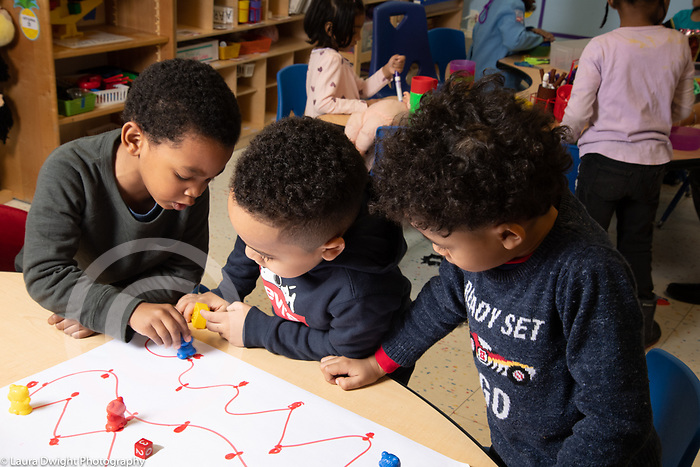 Education preschool three boys playing board game, rolling die and moving bears along a path
