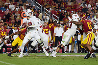 LOS ANGELES, CA - SEPTEMBER 11: Tanner McKee #18 of the Stanford Cardinal looks to pass the ball and Barrett Miller #63 and Walter Rouse #75 provide protection during a game between University of Southern California and Stanford Football at Los Angeles Memorial Coliseum on September 11, 2021 in Los Angeles, California.