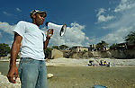 Prelok Pierre Louis (with megaphone), a community health worker for Oganizasyon Sante Popilè (OSAPO), speaks to residents of using the local river to bathe and wash laundry in Montrouis, Haiti, about steps they can take to prevent the spread of cholera, which appeared on the quake-ravaged Caribbean island nation in late 2010. OSAPO's work is supported by Diakonie Katastrophenhilfe and the Lutheran World Federation, both members of the ACT Alliance. Health workers from OSAPO go out to surrounding neighborhoods and communities in teams of three, providing education, distributing anti-bacterial soap and oral rehydration salts, and referring ill patients to the OSAPO clinic...