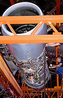 A worker on an engine assembly held in place by orange scaffolding