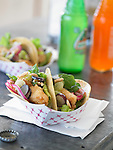 Carry out fish tacos on metal table with fruit sodas