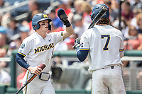 Michigan Wolverines shortstop Jack Blomgren (2) is greeted by teammate Jesse Franklin (7) after scoring during Game 11 of the NCAA College World Series against the Texas Tech Red Raiders on June 21, 2019 at TD Ameritrade Park in Omaha, Nebraska. Michigan defeated Texas Tech 15-3 and is headed to the CWS Finals. (Andrew Woolley/Four Seam Images)