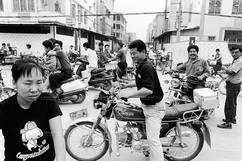 China. Province of Guangdong. The village of Beilin is part of the town of Guiyu. Men and motorbikes, working as motorcycles taxis, are waiting for clients in the city center. © 2004 Didier Ruef