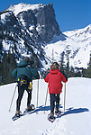 Couple snowshoeing with Hallett Peak in background, Rocky Mtn Nat'l Park, CO